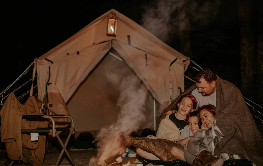 family enjoying camping outside wall tent
