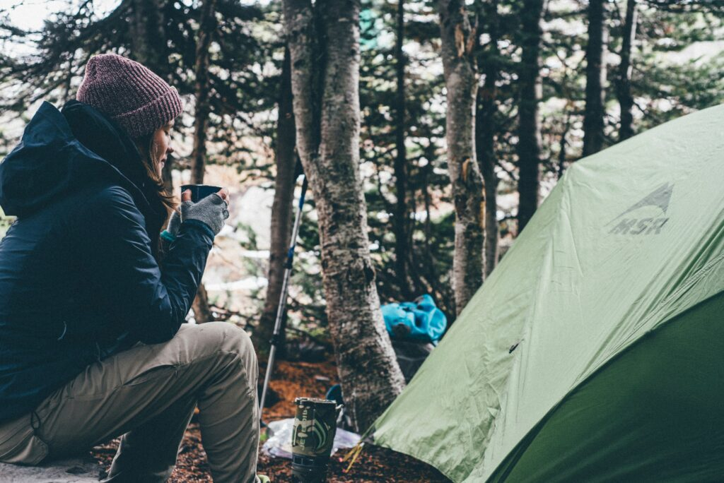 girl having coffee near a tent in outdoors