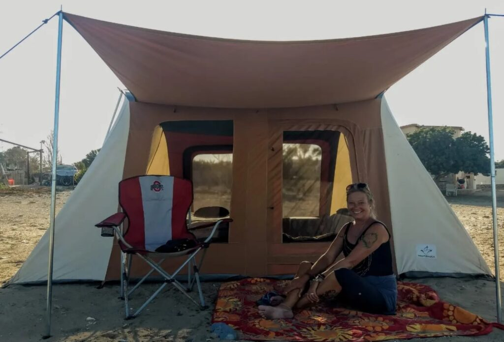 woman sitting outside white duck tent