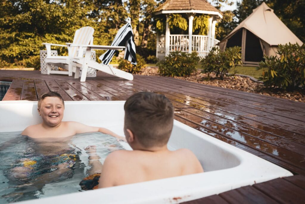 boys in bath tub near glamping tent